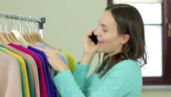 Young excited shopping woman talking at smartphone in clothes store HD - stock footage