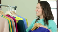Young smiling woman seller put clothing hangers at the rack HD - stock footage
