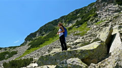 Tourist woman with a backpack stops to admire the beautiful mountain - stock footage