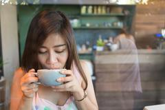 Beautiful girl drinking hot coffee or tea in coffee cafe, model asia women, f Stock Photos