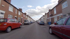 Driving along a town street with parked cars and terraced houses. Stock Footage