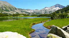 Beautiful lake in the mountain Pirin, Bulgaria, tourist woman passing by Stock Footage