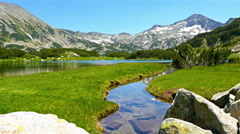 Beautiful lake in the mountain Pirin, Bulgaria, tourist man passing by Stock Footage