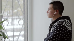 Man listens to music with headphones and looking out the window Stock Footage