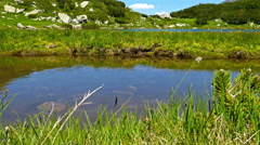 Beautiful lake in the mountain, tourist passing by, her reflection is in water Stock Footage