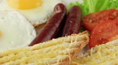 English breakfast with fried eggs, sausages, toasts and tomatoes, closeup (loop) Stock Footage