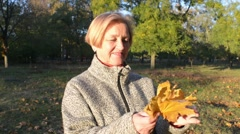 Beautiful Middle Aged Woman In Autumn Park Stock Footage