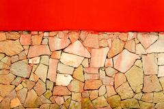 Irregular tiled wall with a red painted wall with copyspace - stock photo