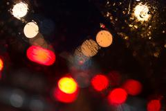 Defocused car lights in a city center with rainwater reflections on the winds - stock photo