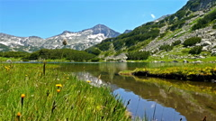 Beautiful lake in the mountain, tourist woman stops to admire the landscape Stock Footage