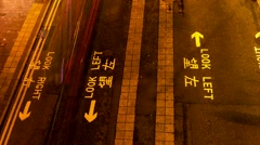 HONG KONG - October 2015: People crossing street in the night. Time lapse pan. Stock Footage