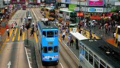HONG KONG - October 2015: Double decker trams and people on crosswalk. 4K Stock Footage