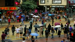 HONG KONG - City traffic and people with umbrellas crossing street. Stock Footage