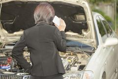 Business woman with her broken car, calling for assistance Stock Photos