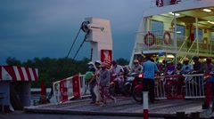 Commuters motorcyclists drive off a ferry across the Nha Be River Stock Footage