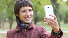 Woman takes selfie shots via smart phone in a park for instagram Stock Footage