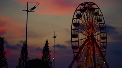 Turning illuminated ferris wheel late in the evening Stock Footage