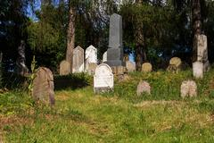 forgotten and unkempt Jewish cemetery with the strangers - stock photo