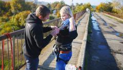 Instructor puts equipment at the girl before a jump Stock Footage