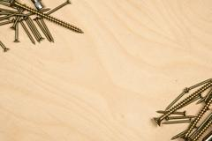 Gold screws diagonally with wood background - stock photo