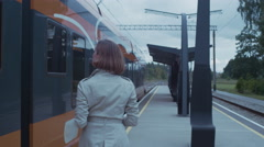 Confident Woman in Trench Walking on Train Station and Getting into Train Doors - stock footage