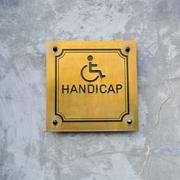 Disabled Handicap Icon and wording Handicap Sign made from gold metal board - stock photo
