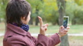 Woman takes selfie shots via smart phone in a park for instagram 4k or 4k+ Resolution