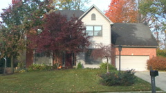 Establishing shot front of a middle class house morning or evening autumn / fall Stock Footage