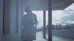 Confident Woman in Trench Walking in Railway Station - stock footage