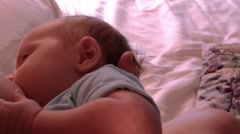 Infant Caucasian baby boy nursing with mother on bed Arkistovideo