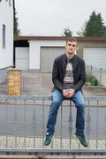 teenager on fence - stock photo