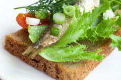 sprats on the bread - stock photo
