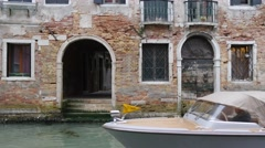 Water taxi passing by in Venitian canal in front of old brick building Stock Footage