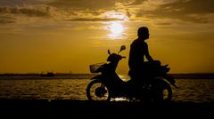 Stock Photo of Silhouette of man sit on motorbike for see sunset sky