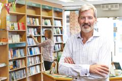 Portrait Of Male Bookstore Owner With Customer In Background Stock Photos