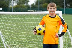 Portrait Of Goal Keeper Holding Ball On School Soccer Pitch Stock Photos