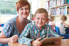 School Pupil With Teacher Using Digital Tablet In Classroom - stock photo