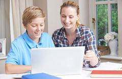 Female Home Tutor Helping Boy With Studies Using Laptop Computer Stock Photos