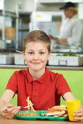 Male Pupil Sitting At Table In School Cafeteria Eating Unhealthy Lunch Kuvituskuvat