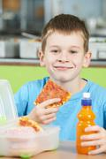Male Pupil Sitting At Table In School Cafeteria Eating Unhealthy Packed Lunch Stock Photos