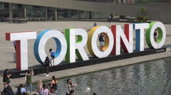 Tourists pose in front of Toronto sign and fountains at the City Hall - stock footage