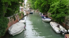 Small motorized boats passing by in Venice canal street Stock Footage