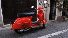 Red moped parked on cobblestone street in Rome, Italy. Stock Footage