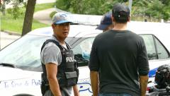 4K UHD - Police and plain clothe officers discussing at crime scene Stock Footage