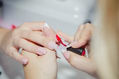 Paint lacquer red nails in beauty salon Stock Photos