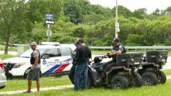 4K UHD - Police officers standing by with ATV's on the grass Stock Footage