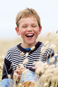 blond child laughing in nature - stock photo