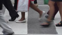 Close up of legs and feet of people crossing road Stock Footage