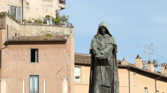 Statue of Giordano Bruno with apartments and gulls in background. - stock footage