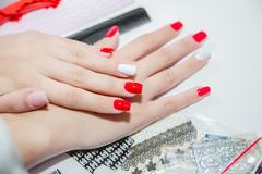 Paint lacquer red nails in beauty salon - stock photo